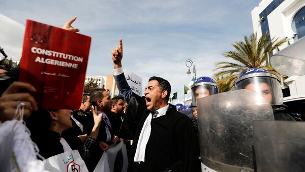 Lawyers chant slogans as they gesture near riot police outside the constitutional council during a protest denouncing an offer by President Abdelaziz Bouteflika to run in elections next month but not to serve a full term if re-elected, in Algiers, Algeria March 7, 2019. - Sputnik International
