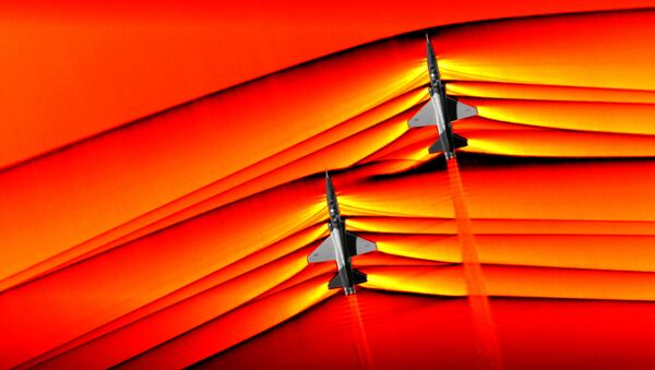 Using the schlieren photography technique, NASA was able to capture the first air-to-air images of the interaction of shockwaves from two supersonic aircraft flying in formation. These two U.S. Air Force Test Pilot School T-38 aircraft are flying in formation, approximately 30 feet apart, at supersonic speeds, or faster than the speed of sound, producing shockwaves that are typically heard on the ground as a sonic boom. The images, originally monochromatic and shown here as colorized composite images, were captured during a supersonic flight series flown, in part, to better understand how shocks interact with aircraft plumes, as well as with each other. - Sputnik International