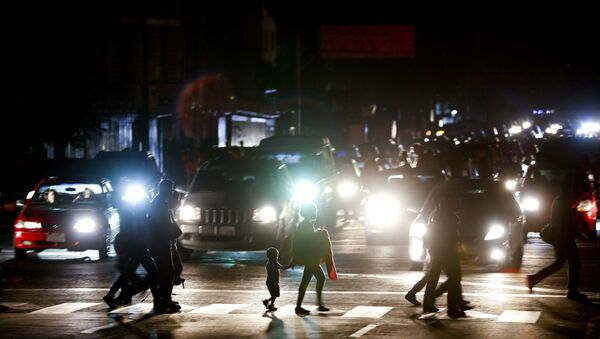 Residents cross a street in the dark after a power outage in Caracas, Venezuela, Thursday, March 7, 2019. A power outage left much of Venezuela in the dark early Thursday evening in what appeared to be one of the largest blackouts yet in a country where power failures have become increasingly common. Crowds of commuters in capital city Caracas were walking home after metro service ground to a halt and traffic snarled as cars struggled to navigate intersections where stoplights were out. - Sputnik International