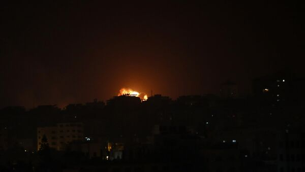 An explosion caused by Israeli airstrikes is seen on Gaza City, early Friday, March 15, 2019. - Sputnik International