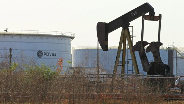 An oil pumpjack and a tank with the corporate logo of state oil company PDVSA are seen in an oil facility in Lagunillas - Sputnik International