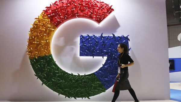 In this Monday, Nov. 5, 2018, photo, a woman carries a fire extinguisher past the logo for Google at the China International Import Expo in Shanghai - Sputnik International