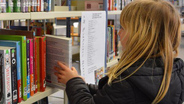 A young girl picking up a book - Sputnik International