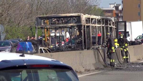 The wreckage of a bus that was set ablaze by its driver in protest against the treatment of migrants trying to cross the Mediterranean Sea, is seen on a road in Milan, Italy, 20 March, 2019 - Sputnik International