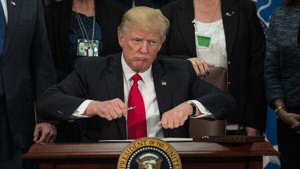 US President Donald Trump takes the cap off a pen to sign an executive order to start the Mexico border wall project at the Department of Homeland Security facility in Washington, DC, on January 25, 2017. - Sputnik International