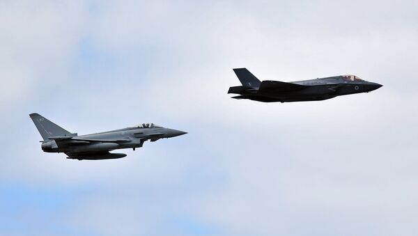 A British Royal Air Force (RAF) Lockheed Martin F-35 Lightning II (R) and a Eurofighter Typhoon aircraft perform a fly-past during the Farnborough Airshow, south west of London, on July 17, 2018 - Sputnik International