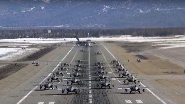 An elephant walk of 24 F-22 Raptor stealth fighters, a C-17 Globemaster III transport plane and an E-3 Sentry command and control surveillance craft take off from Alaska's Joint Base Elmendorf-Richardson base March 26, 2019.  - Sputnik International