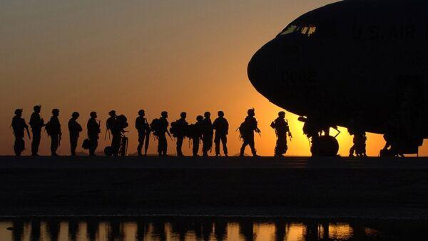 The sun sets behind a C-17 Globemasterat Joint Base Balad, Iraq, as Soldiers begin boarding - Sputnik International