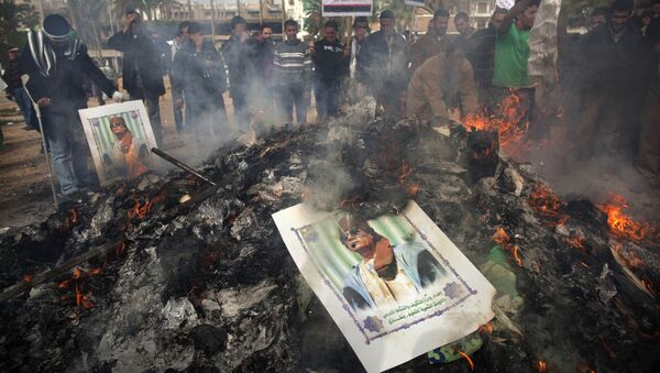 Libyan protesters burn a poster of Libyan leader Moammar Gadhafi as it is burned during a demonstration against him in Benghazi, eastern Libya, Wednesday, March 2 , 2011 - Sputnik International