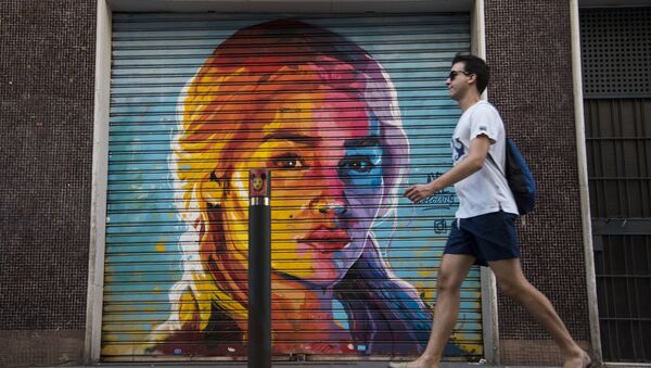 A man walks in front of a graffiti by street artist Axe Colours portraying British actress Emilia Clarke known for playing Daenerys Targaryen in The Game of Thrones TV series in Barcelona on July 30, 2017 - Sputnik International