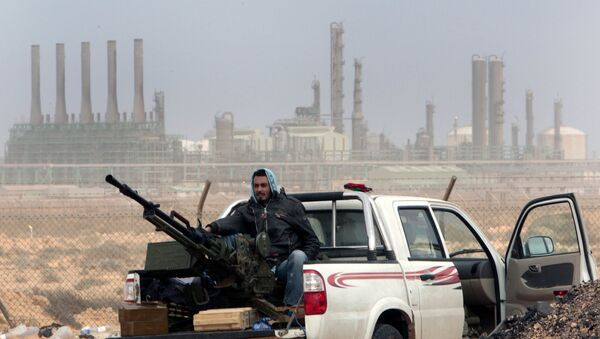An anti-government rebel sits with an anti-aircraft weapon in front an oil refinery in Ras Lanouf, eastern Libya. - Sputnik International