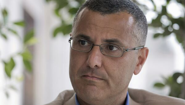 Omar Barghouti listens during an interview with the Associated Press in the West Bank city of Ramallah, Tuesday, May 10, 2016. Barghouti, a Qatari-born Palestinian who is married to an Israeli woman and leader of the international boycott movement against Israel, on Tuesday accused Israeli authorities of imposing a travel ban on him as retribution for his political activities. - Sputnik International