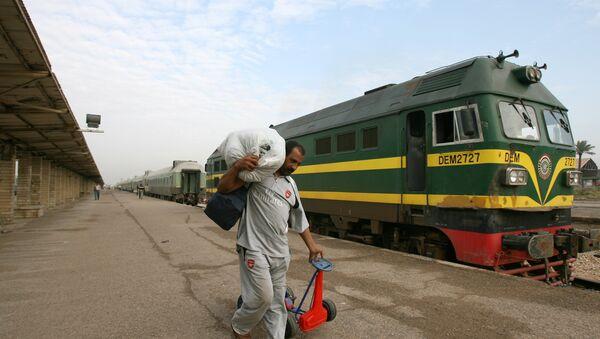 An Iraqi passenger carries his belongings next to a train at the al-Alawi railway station, central Baghdad, Iraq - Sputnik International