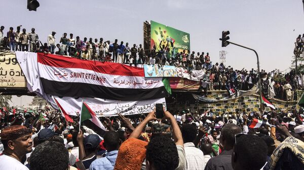 Demonstrators gather in Sudan's capital of Khartoum, Friday, April 12, 2019. The Sudanese protest movement has rejected the military's declaration that it has no ambitions to hold the reins of power for long after ousting the president of 30 years, Omar al-Bashir. The writing on the Sudanese flag says 'With the participation of the Sudanese in Saint Etienne, France.' - Sputnik International