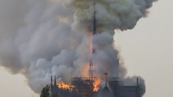 Flames and smoke are seen billowing from the roof at Notre-Dame Cathedral in Paris on April 15, 2019. A fire broke out at the landmark Notre-Dame Cathedral in central Paris, potentially involving renovation works being carried out at the site, the fire service said. - Sputnik International