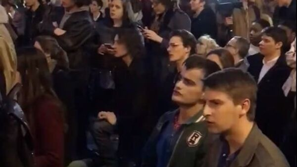 Parisians singing near burning Notre Dame Cathedral in Paris. - Sputnik International