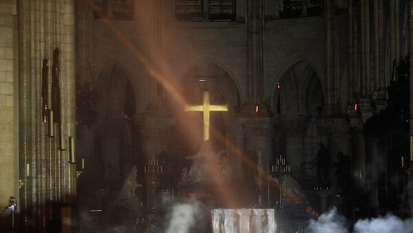 Smoke rises around the alter in front of the cross inside the Notre Dame Cathedral as a fire continues to burn in Paris, France, April 16, 2019. - Sputnik International