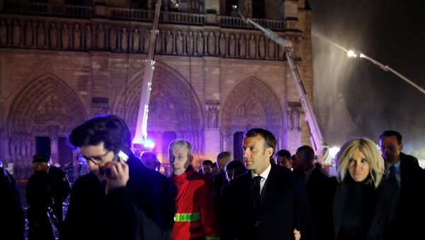 French President Emmanuel Macron and his wife Brigitte walk outside the Notre Dame Cathedral where a fire continues to burn in Paris on April 16, 2019. - Sputnik International
