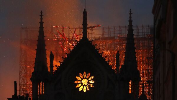 Flames and smoke rise from Notre Dame cathedral as it burns in Paris, Monday, April 15, 2019 - Sputnik International