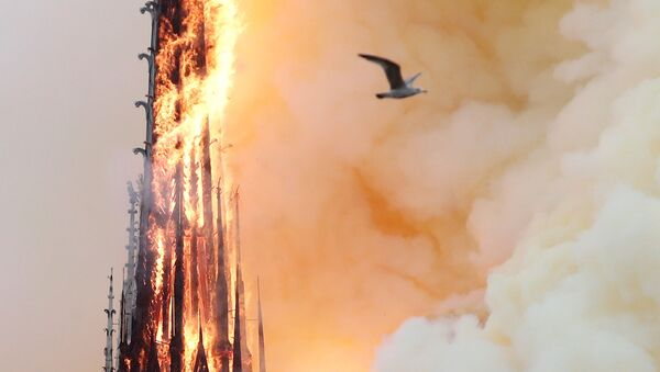 Smoke billows as fire engulfs the spire of Notre Dame Cathedral in Paris, France April 15, 2019 - Sputnik International
