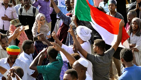 Sudanese demonstrators celebrate after Defence Minister Awad Ibn Auf stepped down as head of the country's transitional ruling military council, as protesters demanded quicker political change, near the Defence Ministry in Khartoum, Sudan April 13, 2019 - Sputnik International