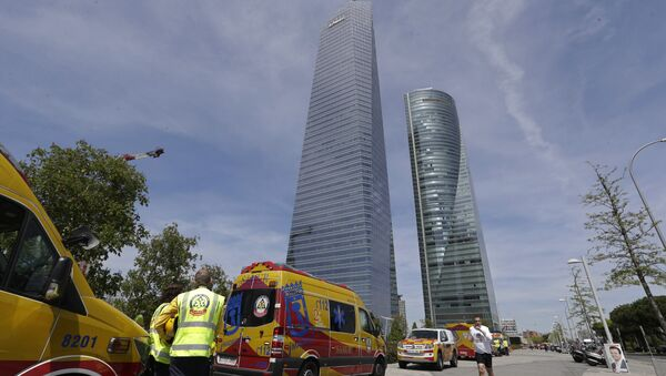 Ambulances wait outside the Torrespacio skyscraper, right, as a jogger runs by in Madrid, Spain, Tuesday, April 16, 2019, after the 57-storey office tower in Madrid's business district that houses several foreign embassies was evacuated due to an unspecified security threat - Sputnik International