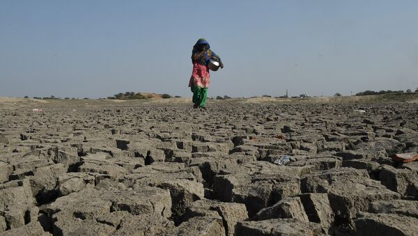An Indian woman walks over the parched bed of Chandola Lake in Ahmedabad on March 22, 2019, on World Water Day - Sputnik International