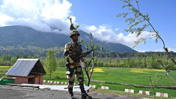 An Indian Border Security Force (BSF) soldier stands guard on the top of a polling station during a second phase of elections at Kangan, some 35 km from Srinagar on April 18, 2019 - Sputnik International