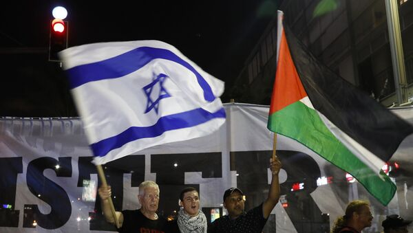 Arab Israelis and their supporters carry a Palestinian (R) and an Israeli flag during a demonstration to protest against the 'Jewish Nation-State Law' in the Israeli coastal city of Tel Aviv on August 11, 2018. - Sputnik International