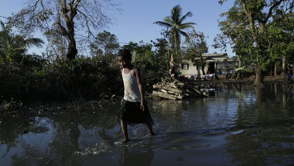 a young girl walks through flood waters near Beira, Mozambique, March 26, 2019, in one of the world's areas most vulnerable to global warming's rising waters - Sputnik International