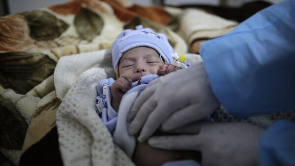 a doctor checks a two-month-old infant suffering from a cholera infection, at Al-Sabeen hospital, in Sanaa, Yemen, on March 30, 2019 - Sputnik International