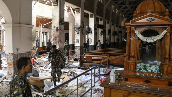 Sri Lankan security personnel walk past dead bodies covered with blankets amid blast debris at St. Anthony's Shrine following an explosion in the church in Kochchikade in Colombo on April 21, 2019. - Sputnik International