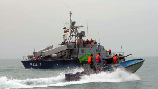 A picture released by the official Iranian News Agency shows members of Iran's elite Revolutionary Guard riding their boat along with an Iranian naval vessel during manoeuvers along the Gulf Sea and Sea of Oman, 03 April 2006 - Sputnik International