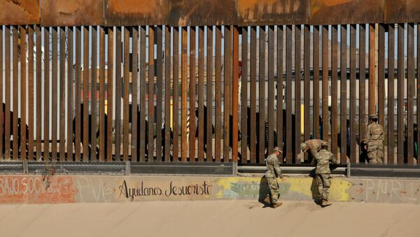 U.S. soldiers walk next to the border fence between Mexico and the United States, as migrants are seen walking behind the fence, after crossing illegally into the U.S. to turn themselves in, in El Paso, Texas, U.S., in this picture taken from Ciudad Juarez, Mexico, April 3, 2019 - Sputnik International
