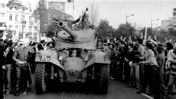 People cheer Portuguese soldiers in a tank driving in Lisbon during the Carnation Revolution in 1974 - Sputnik International