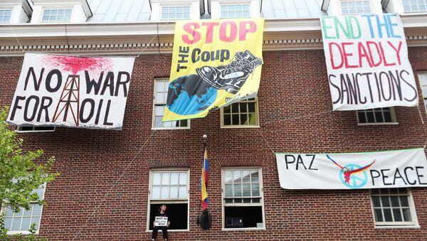 An activist in opposition of the U.S. involvement in Venezuela occupying the Venezuelan Embassy, sits in a window sill in Washington - Sputnik International