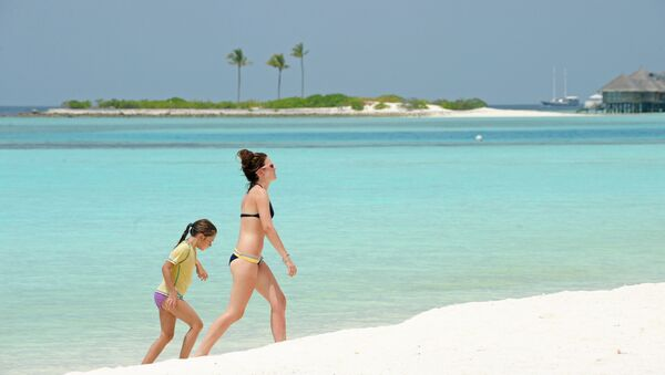 Unidentified foreign tourists walk along a beach of the Paradise Island Resort and Spa in the North Male' Atoll on February 14, 2012 - Sputnik International