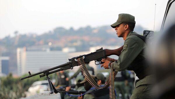 A military member aims a weapon near the Generalisimo Francisco de Miranda Airbase La Carlota, in Caracas, Venezuela April 30, 2019 - Sputnik International
