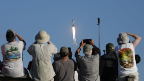 Visitors at Playalinda Beach look on as a SpaceX Falcon Heavy rocket launches from Pad 39B at the Kennedy Space Center in Florida, on April 11, 2019 - Sputnik International