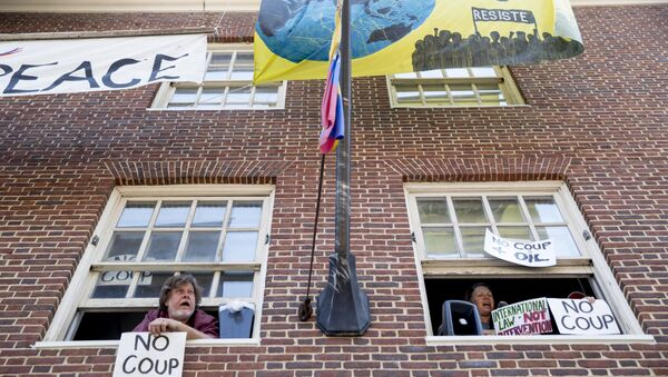 Pro Nicolas Maduro supporters look out the windows of the Venezuelan Embassy in Washington, Thursday, May 2, 2019. Pro interim government opposition leader Juan Guaido supporters have blocked the entrances to the embassy, cutting off supplies to pro Nicolas Maduro supporters occupying the building. - Sputnik International