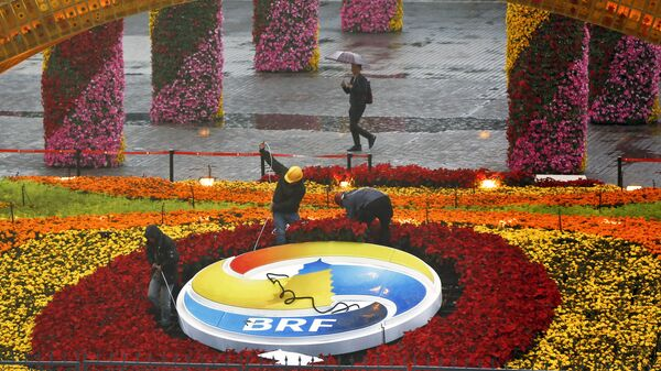A man carrying an umbrella to shield from the rain as workers dismantle the Belt and Road Forum logo outside the media center as leaders are attending the round table summit of the Belt and Road Forum chaired by Chinese President Xi Jinping in Beijing, Saturday, April 27, 2019 - Sputnik International