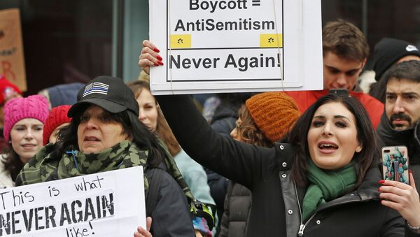 Political activist Laura Loomer, right, holds a sign across the street from a rally organized by Women's March NYC after she barged onto the stage interrupting Women's March NYC director Agunda Okeyo who was speaking during a rally in Lower Manhattan, Saturday, Jan. 19, 2019, in New York. Loomer was escorted off the stage after the incident - Sputnik International