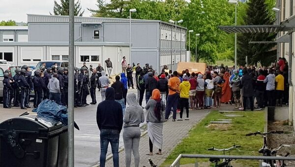 German police officers and migrants stand in front of an asylum center after a woman was found dead in the center in Regensburg, Germany, Saturday, May 11, 2019 - Sputnik International
