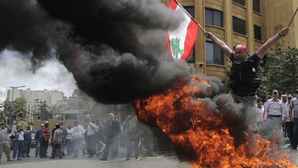A Lebanese retired soldier holds a Lebanese national flag as he jump over burning tires during a protest in front of the government building during a cabinet meeting to discuss an austerity budget, in Beirut, Lebanon - Sputnik International