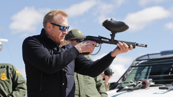 In this Feb. 23, 2019, photo, acting Secretary of Defense Patrick Shanahan, center, fires a modified painted ball gun that shoots pepper balls during a tour of the US-Mexico border at Santa Teresa Station in Sunland Park, N.M., Saturday, Feb. 23, 2019. Shanahan, the former Boeing executive, was in a familiar place, aboard an airplane, when he got word of a bolt-from-the-blue political shot across his bow. A key senator seemed to have buried Shanahan's chances of being nominated as the next secretary of defense. The crisis passed, but it highlighted the precarious position Shanahan occupies as he waits for President Donald Trump to decide who he will successor to Jim Mattis as leader of the Pentagon. (AP Photo/Pablo Martinez Monsivais) - Sputnik International