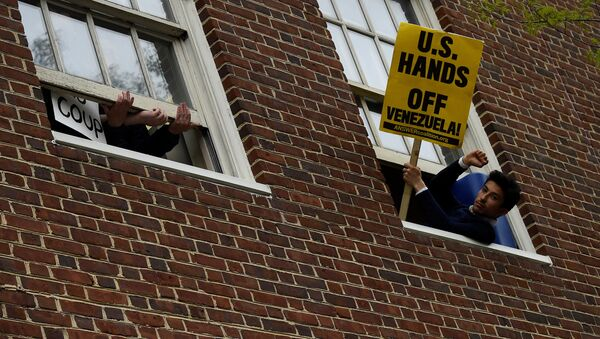 A man holds a sign outside the window of the Venezuelan embassy which is occupied by Nicolas Maduro supporters as Venezuelan opposition leader Juan Guido's envoy to the United States Carlos Vecchio speaks outside in Washington, U.S., May 1, 2019 - Sputnik International