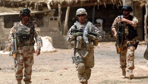 U.S. Army Capt. Eric Morton, center, commander of the 101st Airborne Division's Company B, 1st Battalion, 35th Armor Regiment, walks with Iraqi Maj. Ahmed Hassan and Iraqi 1st Lt. Yasev Mutasam through Shakriyah, Iraq, area during Operation New Town, June 10, 2008 - Sputnik International