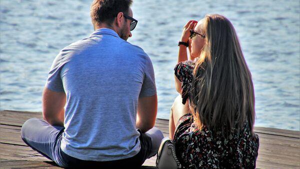 Couple talking while sitting on a dock - Sputnik International