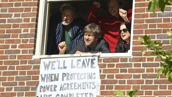 The four activists inside the Venezuelan embassy in Washington look outside the window from a second floor on Tuesday, May 14, 2019. Clockwise from left: Kevin Zeese, Margaret Flowers, Adrienne Pine, and David Paul. - Sputnik International