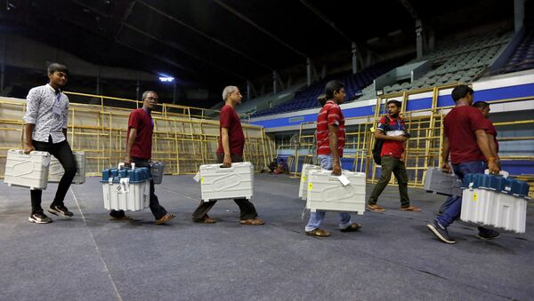 FILE PHOTO: Members of election staff carry Electronic Voting Machines (EVM) and Voter Verifiable Paper Audit Trail (VVPAT) machines after collecting them from a distribution centre at an indoor stadium ahead of the seventh and last phase of general election, in Kolkata, India, May 18, 2019. - Sputnik International